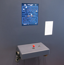 A screen on a plain gray wall displaying Pac-Man, with a simple joystick and pair of headphones beneath it