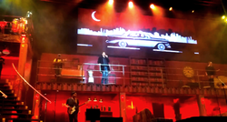 Singer on stage balcony flanked by musicians, below classic car on TV screen