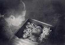 A black and white image of the film depicting a transparent Allan Gray looking at his own body that is lying in a coffin.