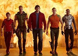 Five men walk away from an exploding building. Each man is dress in an individual costume. From the left, the first man wears an all red outfit with yellow lightning bolts down the side. The second man wears a green, leather outfit. The third man wears a red jacket over a solid blue shirt. The fourth man wears a sleeveless wetsuit, with an orange top and green bottom. The final man wears a silver vest over a black spandex top and bottom.
