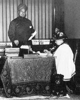 Queen Victoria's journals - Queen Victoria, attending to her correspondence. She is attended by her Indian secretary, Abdul Karim (the Munshi), and her favourite collie, Noble.