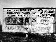 "A black and white photograph of a billboard with pictures of five children and large text asking ""What was their fate? Murdered? Kidnapped? Or are they still alive?"" and ""$5000 reward"""