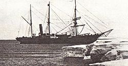 Three-masted ship with funnel to rear, anchored by the bow to an ice shelf