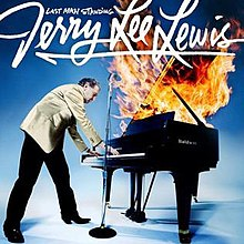 Lewis standing over a piano engulfed in flame with the name of the artist and album in white script above