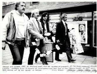 Grey Organisation - Police raid on the exhibition Money, Young Unknowns Gallery, London, 1986. A work by GO can be seen held in the left hand of the policeman second-closest to the camera