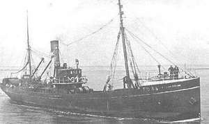 A black-and-white photo showing a little trawler stationary in the water.