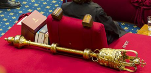 """Woolsack - The Woolsack in 2016, showing the Ceremonial mace. The mace was originated in France by Phillip II circa 1180, and taken up by the English Parliament some time after the coronation of Richard I in 1189. The original mace was a military weapon introduced for the purpose of protecting """"the King's person"""" when he attended parliament, and wielded by the Sergeant-at-Arms, an Office that still exists today, though only in a ceremonial context.."""