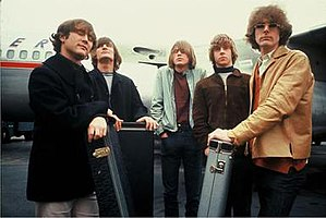 A photograph of five young men with moptop haircuts, looking windswept and standing in front of a passenger airplane. The five are all dressed in casual jackets and jeans, and three of them are resting their hands on guitar cases.