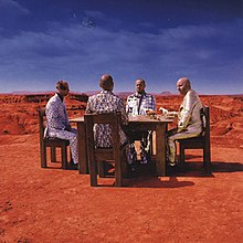 Four men sitting in a table at the Grand Canyon with horses on the table and the earth in the background