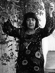 Ida Kar a few months before her death, in a flowery dress with her arms raised