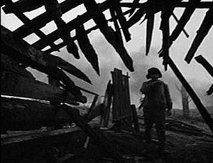 Ivan's Childhood - Ivan in a destroyed village. Broken timber beams look like they are cutting into the picture and toward the main character.