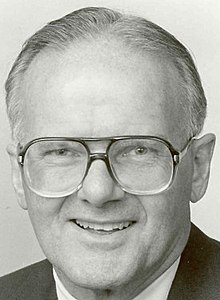 Posed head-shot photograph of Hunt wearing large metal-framed eyeglasses and smiling