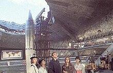 Grotere onderaardse missile silo met een raket wijzen het gat naar de lucht naast een draagconstructie.  Vijf tekens staan op de voorgrond.