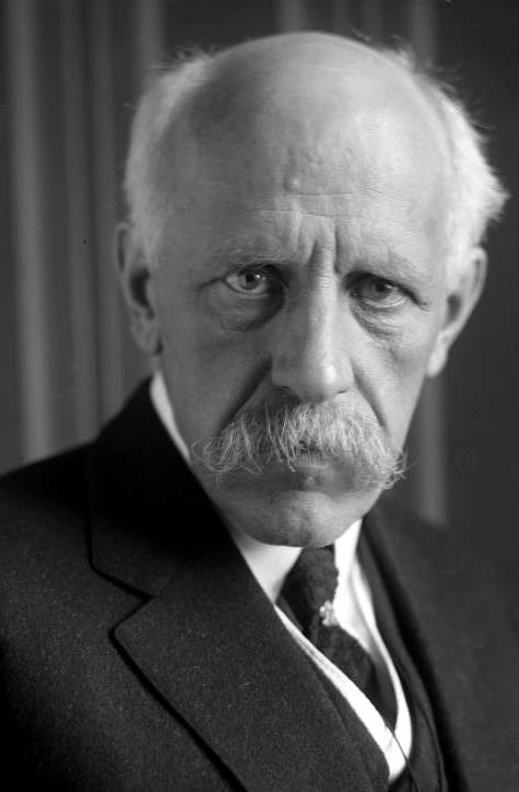 Nansen shown in later years with white, receding hair; characteristic drooping white mustache; and intensely focused eyes.