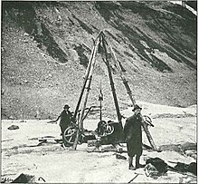 A man standing on a glacier with a drilling rig and a mountain ridge behind him.