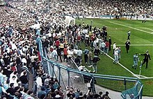 Liverpool Fans Desperately Try To Climb The Fence Onto The Safety Of The Pitch While Being Stopped By The Police