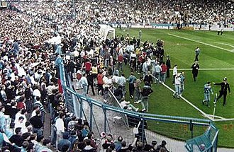 Hillsborough disaster - Liverpool fans desperately try to climb the fence onto the safety of the pitch while being stopped by the police.
