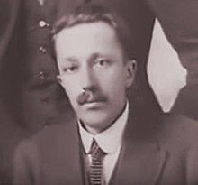 Black and white photograph of a young man with a moustache, dressed in a jacket and tie