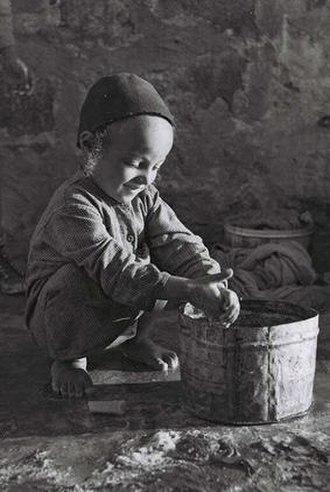 Handwashing in Judaism - Boy in camp rubs his hands after washing them