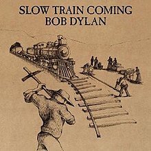 A black line drawing on brown of men building a railroad with a train riding on it toward the viewer