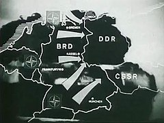 Outline map of Belgium, the Netherlands, West Germany, East Germany and Czechoslovakia with arrows indicating the direction of a hypothetical NATO attack from West Germany into East Germany and Czechoslovakia. An advancing tank is shown in the background behind the map.