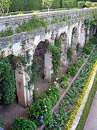 An old Italian wall surrounded by flowers.