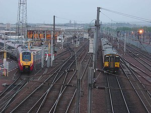 """Polmadie - Polmadie train depot. The West Coast Main Line tracks are on the right, with a Class 318 train running on the fast line to the right. A Virgin """"Voyager"""" train is entering the stabling area to the left, the slow line. This photograph predates the construction of the M74 Extension, which runs to the immediate north of the facility"""