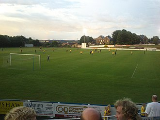 Stocksbridge Park Steels F.C. - The south-west corner of the ground, with club house (left), the pitch and main stand (centre), and the view looking north-east from the clubhouse (right)