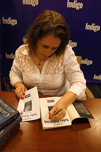 Kelley Armstrong - Armstrong signing autographs for a fan at a book signing.