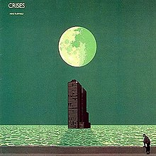 A green coloured seascape with a large moon in the upper centre of the image above a tower building rising out of the sea. The building casts a shadow from the moonlight onto the water. At the bottom of the image a man stands with one foot on a wall.