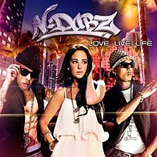 A portrait of three young adults walking in an urban environment at night. On the left and right are young men wearing sunglasses, and in between them is a brunette woman in a white dress. Above them is a N-Dubz logo in white and below it is the title 'Love.Live.Life' in white capital letters.