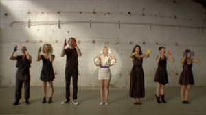 """Soon We'll Be Found - Sia signs """"turn around"""" in her music video with other actors."""