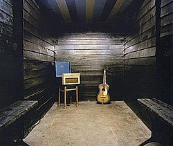 Small area with three black wooden walls; only an amplifer, speaker and guitar can be seen.