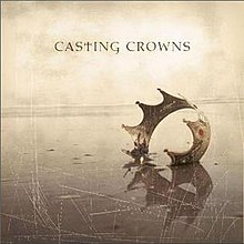 On a tan, scratched screen, a single crown lies embedded in the ground. Above it are the words 'Casting Crowns', with the lowercase 't' replaced with a Christian cross.