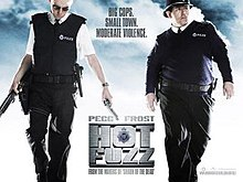 Film poster of two men dressed as British police officers. The man on the left is looking down and is holding a shotgun and a handgun. The man on the right is behind the man on the left with a shotgun and toothpick in his mouth and a explosion behind them. Poster has the films title and the main stars names.