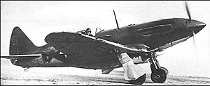 A dark-camouflaged single-engined fighter with an inline piston engine