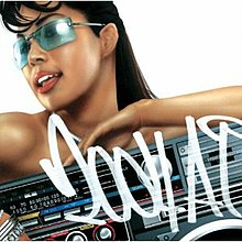 "A mid-shot of Ai against a white background, where she smiles, wearing long hair and blue tinted glasses. She is not noticeably wearing clothes, however the lower half of her body is covered by a boombox. ""2004 A.I."" is hand-written in front of the image in white, in a graffiti-style font."