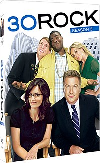 "Two men in suits, a black man in a yellow jacket, a blond woman in green, and a brunette woman in black with glasses on a box labeled ""30 ROCK SEASON 3"""