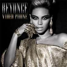 Beyoncé wearing a golden cloth with bare left shoulders. Her right hand is held across her right cheek, and she wears a number of golden rings and metallic contraptions around her fingers. She has dark make-up around her eyes and her hair is pulled back on the top.