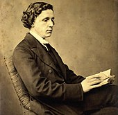 Photographic portrait of Charles Lutwidge Dodgson (Lewis Carroll), seated and holding a book