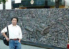Asian male wearing white shirt and jeans in front of a bronze relief sculpture depicting people, tanks and a statue holding a torch; building with an official Chinese Government emblem is in the background