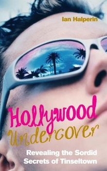 Cover has a close up of a man's face, with palm trees and a sunset reflected in the lens of his dark glasses