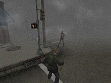 A screenshot from a video game. On the corner of a foggy street, a monster with no arms faces a man in a green jacket wielding a pipe.