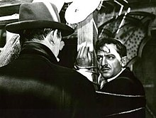 A screen capture from the film, showing a distraught César tied up to a pole staring at Tony le Stéphanois, who has his back to the camera.