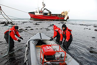 Coast Guardsmen preparing to transport a portable pump to the 112-foot grounded fishing vessel Mar-Gun, March 7, 2009 Ship Ground.jpg