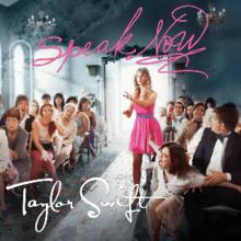 Una joven mujer rubia, vestida con un vestido de cóctel de color rosa, de pie en medio del pasillo de una iglesia con personas sentadas a su lado, muchos de ellos con rostros atemorizados.  Ella tiene su mano extendida hacia el frente como una mujer cerca de sus puntos en indignación.