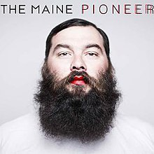 An adult man with a bushy beard, red lips and a white shirt is front-and-centered on the grey cover. The band name appears above the man, along with the album title that's colored twice: one in black and one in red over it.