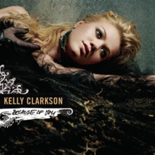 "An image of a blond woman wearing black voluminous dress lying down with her head resting on her left hand, looking aside. At her right, the words ""Kelly Clarkson"" and ""Because of You"" are written in yellow and black capital letters respectively."