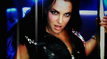 Image of the upper body of a brunette woman wearing a leather vest. She is grabbing a pole with her left hand.