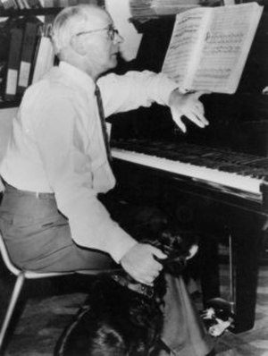 Erik Chisholm - Composing at his Petrof piano with Towser, his concert-going Spaniel, at his feet.